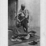 maurischer Barbier rasiert Kunden den Kopf im Stehen