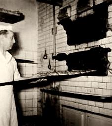 altes sw-Foto: Bäcker schiebt Brote in den Ofen
