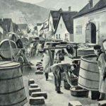 Die Dorfkelterer haben große Weinfässen und Pressen auf der Straße aufgebaut