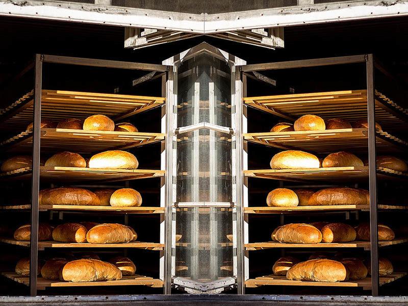 Farbfoto: Brotstiegen mit frisch gebackenem Brot stehen am offenen Fenster. Das Bild ist horizontal gespiegelt.