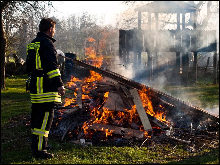 Foto: brennende Holzscheite, Feuerwehr überwacht das Ganze
