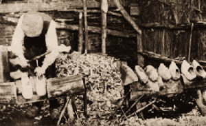 altes s/w Foto: Holzschuhmacher in einem Holzverschlag beim Aushöhlen von Holzpantinen