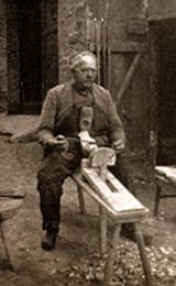 s/w Foto: Holzschuhmacher auf Haubock mit Blockmesser bei der Arbeit