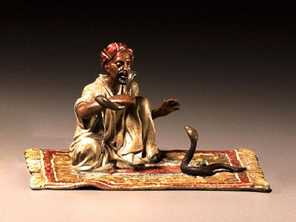 Bronzefigur: dunkelhäutiger Schlangenbeschwörer sitzend auf einem Teppich, auf dem sich vor im eine Schlange empor reckt