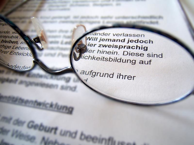 Foto: Brillengestell liegt auf Text und durch die Brillengläser ist er scharf zu lesen