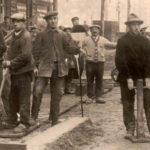 sw-Foto: einige Straßenarbeiter mit Schippen und anderen Werkzeugen schauen in die Kamera