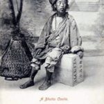 zerlumpter Mann sitzt auf einer Holzkiste, neben ihm ein Korb