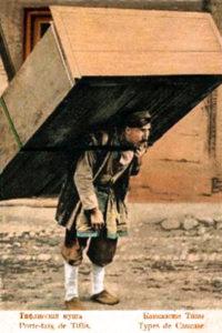 Farbfoto. kaukasischer Mann trägt einen Schrank auf seinem Rücken