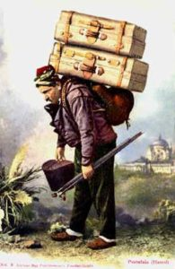 Farbfoto: Mann trägt zwei Koffer auf dem Rücken und weiteres Gepäck in den Händen