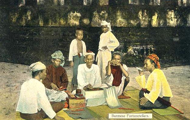 koloriertes Foto: Menschen sitzen um Wahrsager herum auf Teppichen