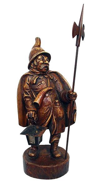 Holzschnitzarbeit: lustiger Nachtwächter im Umhang mit Helm, Hellebarde, Laterne, Horn und Flasche in der Jackentasche