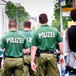"""Farbfoto: Rückansicht: drei Polizisten mit weißer Aufschrift """"Polizei"""" auf grünem Shirt"""