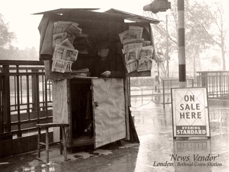 sw-Foto: älterer Mann sitzt unter einer Holzbuden ähnlichen Überdachung, neben ihm Zeitungsaushänge zum Verkauf, aber kein Käufer in Sicht - es regnet ...