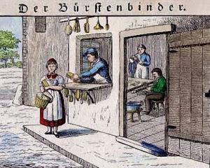 kolorierter Holzschnitt: Blick in die Bürstenbinderwerkstatt, draußen kauft Frau eine Bürste