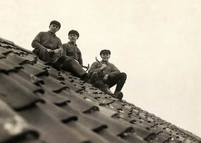 sw-Foto: drei Dachdecker sitzen auf dem fertig gedeckten Dach