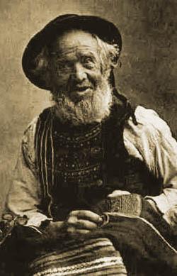 altes Foto: alter Schneider mit Bart und Hut beim Nähen