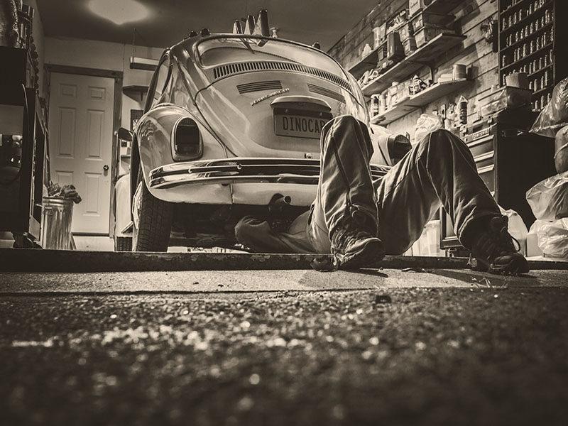 s/w Foto: Autowerkstatt, Mechaniker liegt unter einem VW-Käfer