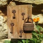 altes Schloss und Schlüssel angehängt an einem Holzbrett als Firmenzeichen