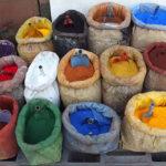 Farbfoto: nebeneinander gestapelte offene Säcke mit verschiedensten Farbpulvern und Schäufelchen sowie rechts eine Waage