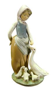 Porzellanfigur: Gänsemagd mit Kopftuch füttert Gans mit Küken