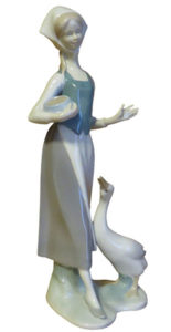 Porzellanfigur: sehr schlanke Gänsemagd mit weißem Kopftuch und blauem Mieder, Futtergefäß im Arm und sich hoch streckende Gans