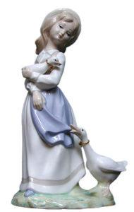 Porzellanfigur: elegante spanische Magd mit blauer Schürze und Strohhut. ein kleine Gans auf dem Arm und größere an Kleidung zupfend