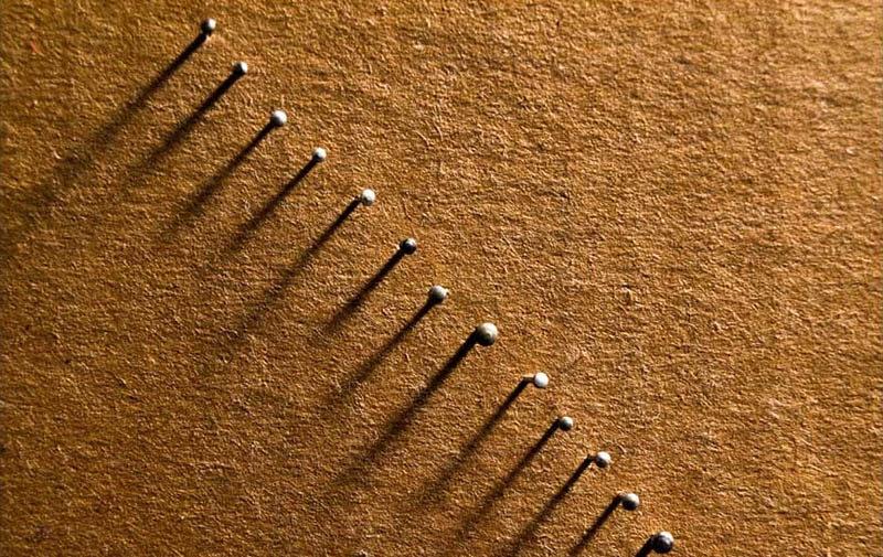 Farbfoto: Stecknadeln in einer Diagonale festgesteckt