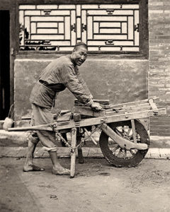s/w Foto: Chinese schärft Messer auf einem flach liegenden Wetzstein, der auf einer Leieterrost-Schubkarre aufliegt