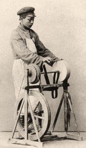 sw Postkarte: junger Scherenschleifer arbeitet stehend an einem Schleifgerät mit Fußpedal