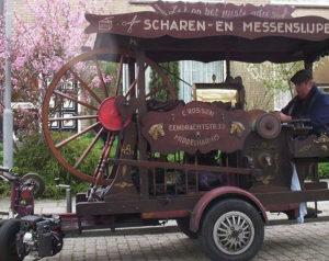 Farbfoto: niederländischer Scheren- und Messerschleifer mit lustigem fahrbaren Untersatz als mobiler Arbeitsplatz