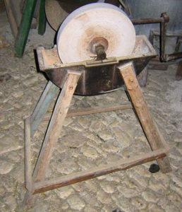 Farbfoto: historisches Bockgestell mit Schleifsteinscheibe in halbrunder Wasserwanne aus Metall