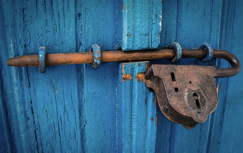 Farbfoto: großes antikes Riegelschloß an blauer Holztür