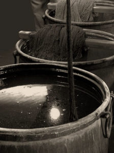 Foto: drei Färbebottiche mit Wolle, die schwarz gefärbt wird