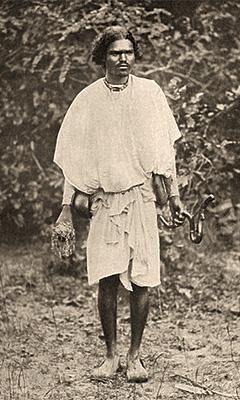 sw Foto: stehender Mann mit Eisenzeug an und in den Händen - 1907