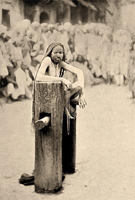 sw Foto: auf Holzbalken hockender Hindu mit sehr langen Haaren - 1907