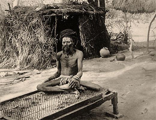 sw Foto: Fakir sitzt im Freien auf Nagelbett