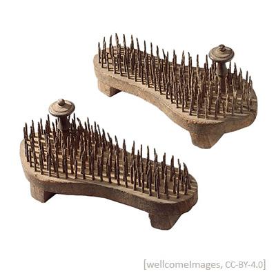 Farbfoto: Holzsandalen mit nach oben gerichteten Nägeln