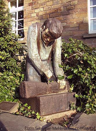 Holzfigur: Bessemsbenger bindet knieend Ruten zu einem Besen
