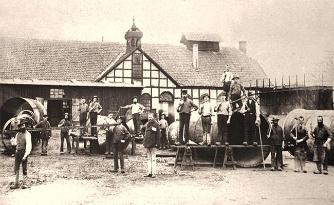 sw Foto: Gruppenbild vor großen Kesseln im Hof der Schmiede