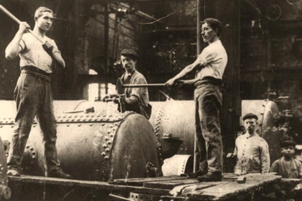 sw Foto: große Industriekessel werden von mehreren Männern gleichzeitig bearbeitet