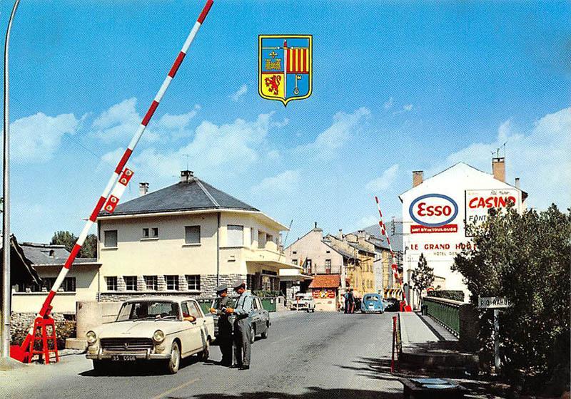 zwei Zöllner stehen an einem Auto am geöffneten Schlagbaum
