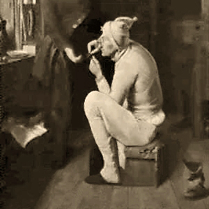 sw Gemäldefoto: auf Kiste sitzender Kleiderflicker näht an Hose eines vor ihm stehenden Mannes
