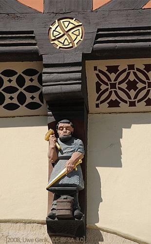 Farbfoto: Holzfigur auf Balkenkopf mit Schwert und Hammer am Amboss