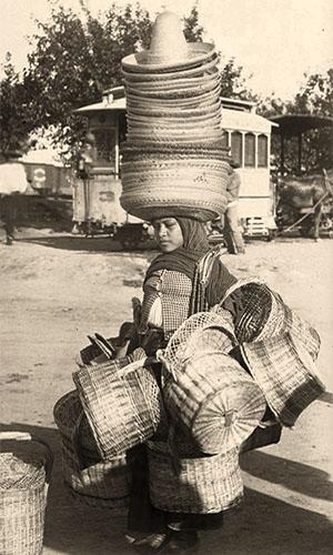 sw Foto: Frau mit Strohutturm auf dem Kopf und vielen zusammengebunden Körben