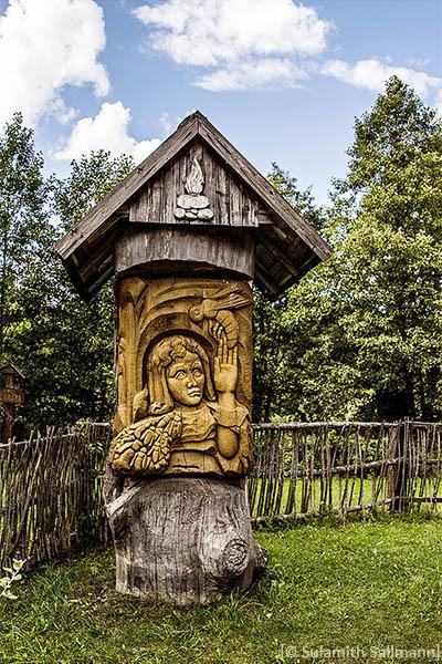 Farbfoto: Baumstamm mit Dach, mittig Holzrelief mit einfliegenden Bienen und Frauenbüste