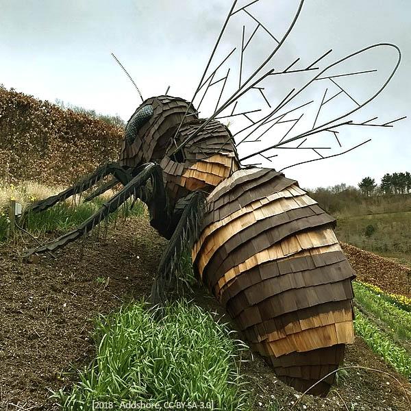 Farbfoto: Riesenbiene aus Spanholz und Draht zwischen Beeten