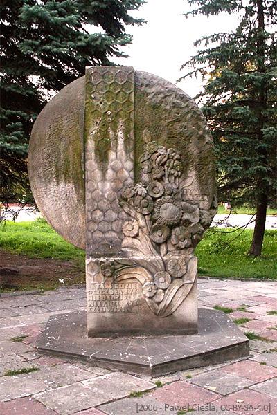 Farbfoto: Skulptur aus Sandstein mit Waben, Blüten und Bienen