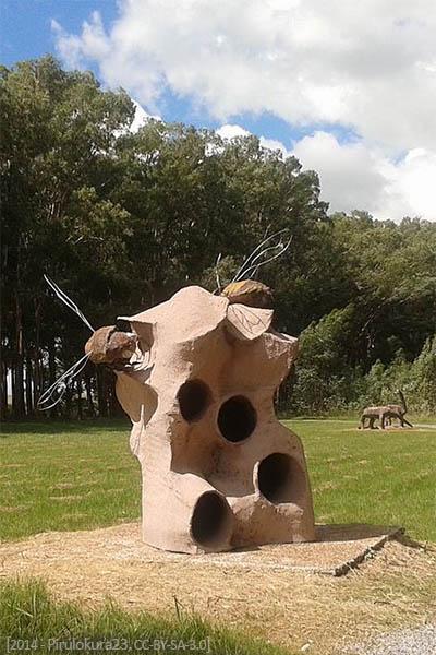 Farbfoto: Bienenbau mit Einfluglöchern aus Sandstein und Holzbienen mit Drahtflügeln in Park in Uruguay