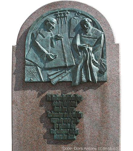 Bronzerelief zeigt Tuchmacher und Schneider + Text