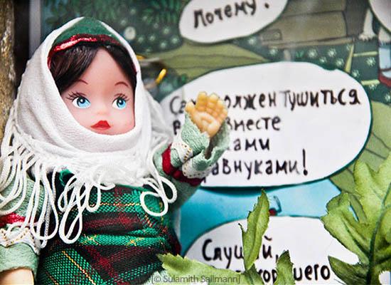 Farbfoto: winkende russ. Puppe mit Kopftuch sitzt vor Sprechblasen